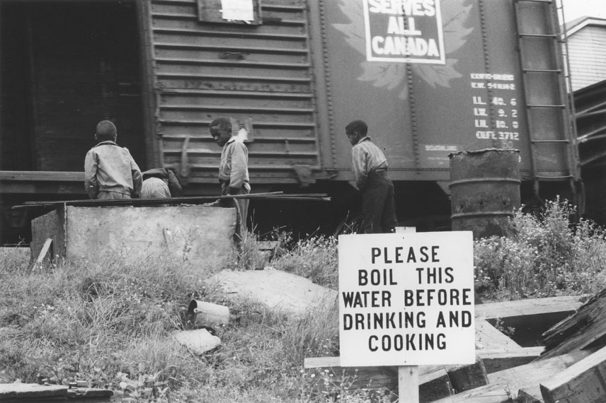 Boys beside Canadian National railcar, Africville, with Please boil this water before drinking and cooking sign in foreground
