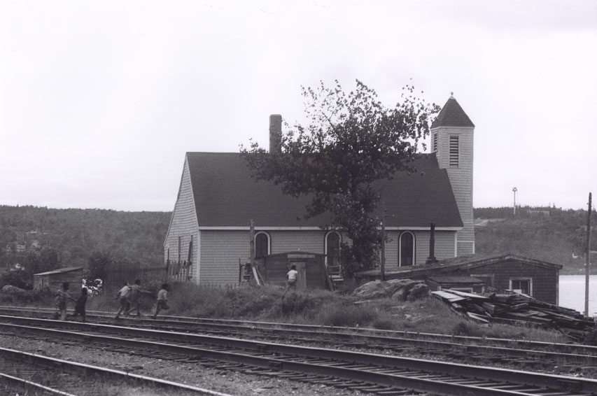 Boys crossing railroad tracks towards Seaview African United Baptist Church, Africville c.1965