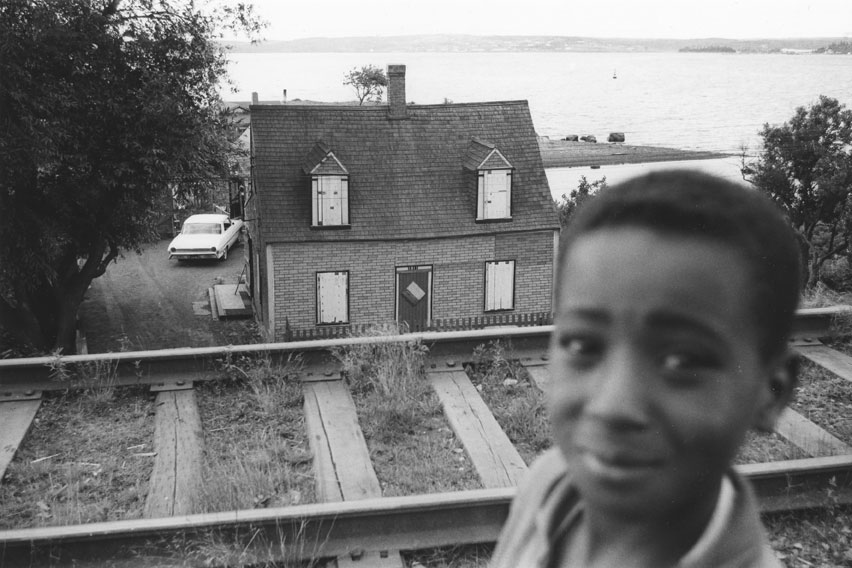 Young boy, with Ralph Jones' house, Africville, boarded up prior to demolition, in the background